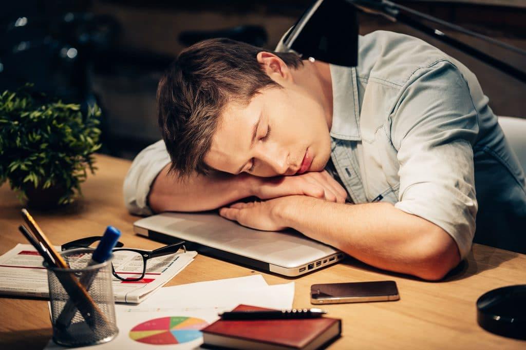 Homem jovem, cansado, dormindo debruçado em cima de um notebook fechado em cima de uma mesa de trabalho.
