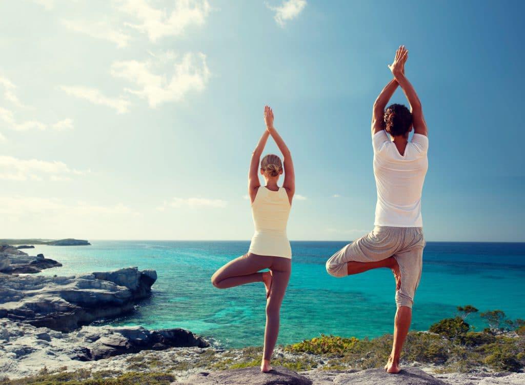 Homem e mulher, ambos brancos, praticando yôga em uma praia paradisíaca, observando o mar