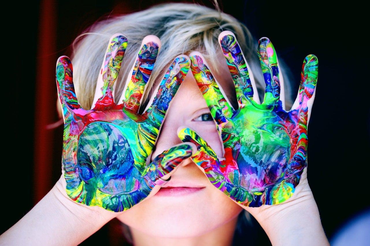 Criança com as mãos coloridas de tinta na frente do rosto