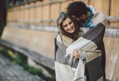 Casal enrolado em um cobertor no foco com mulher sorrindo e homem com cabeça apoiada no cabelo dela