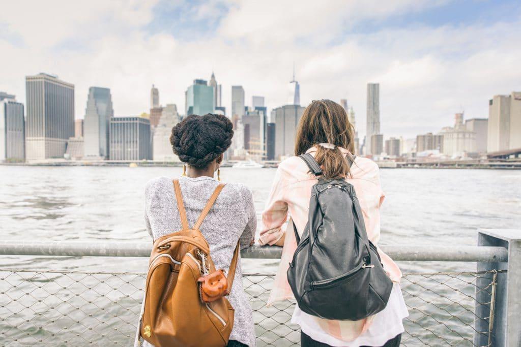 Duas mulheres, uma negra e uma branca, lado a lado, observando uma paisagem urbana de prédios, próximas à um rio