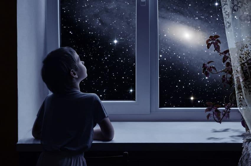 Menino olhando pras estrelas pela janela