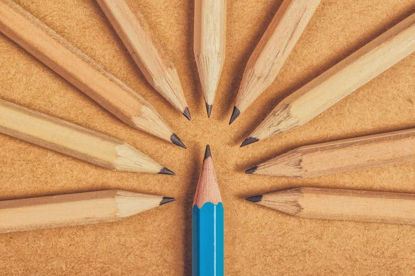 Lápis azul cercado de lápis sem cor