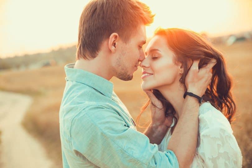 Casal em um campo aberto ensolarado. O homem segura o rosto da mulher bem próximo ao seu e ambos sorriem.