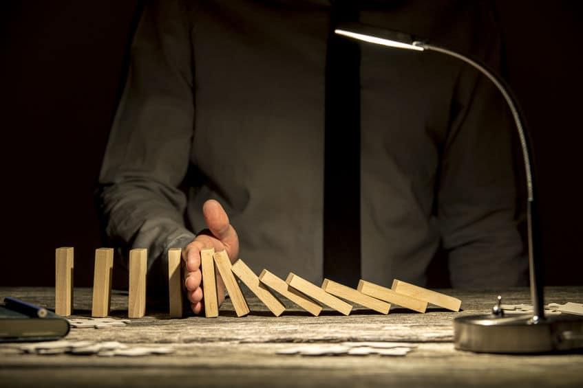 Visão de frente de um homem de negócios parando peças de dominós que estão caindo com a mão