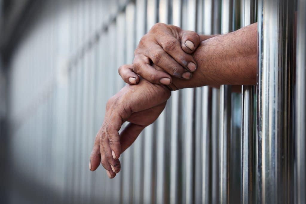 Mãos de um homem, sujas, colocadas para o lado de fora das barras de uma cela