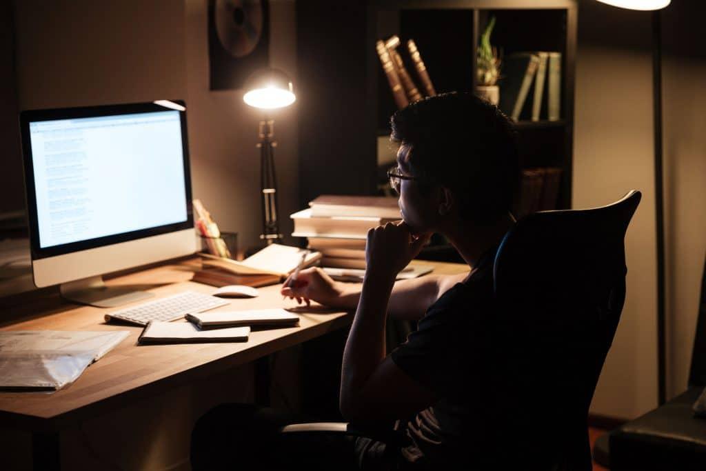 Homem sentado em uma mesa de escritório, olhando para tela de computador, tomando nota em um pequeno caderno