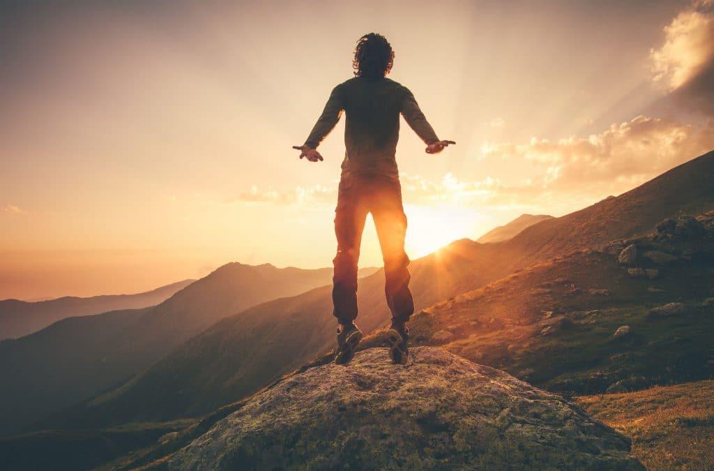 Homem em pé em uma montanha com o sol se pondo atrás.