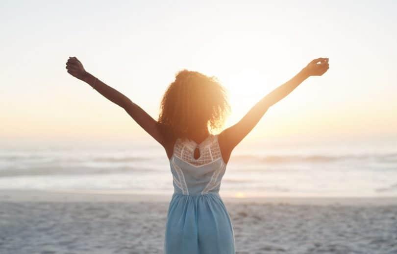 Mulher de costas com braços abertos de frente para pôr-do-sol na praia