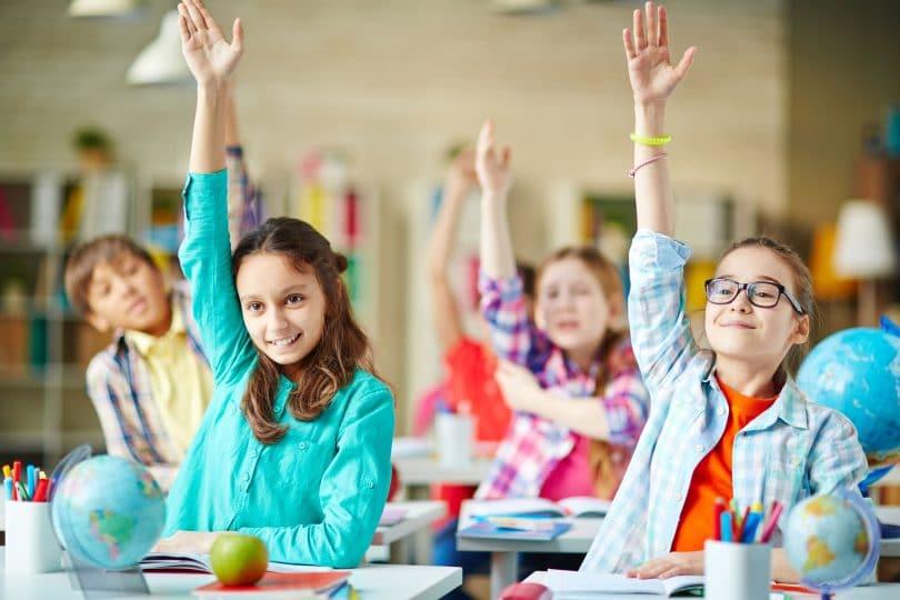 Crianças na sala de aula levantando a mão com sorriso no rosto