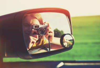 Meninha com máquina fotográfica vista pelo retrovisor de um carro