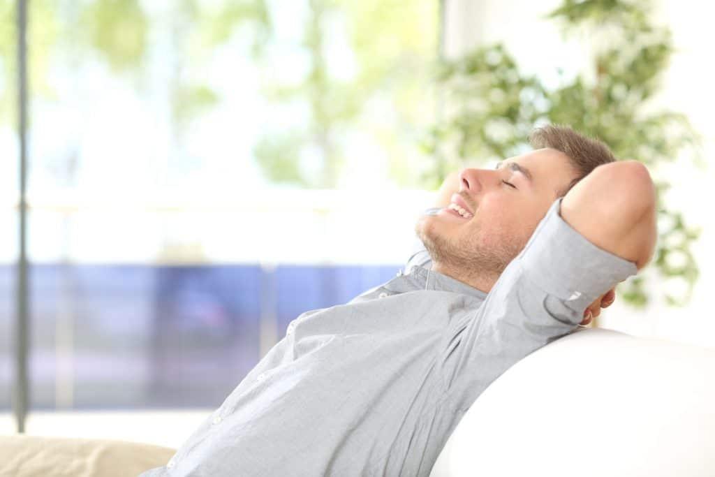 Homem branco, sorridente, sentado em um sofá branco, relaxando enquanto se espreguiça.