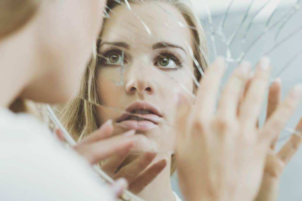 Mulher encarando um espelho quebrado