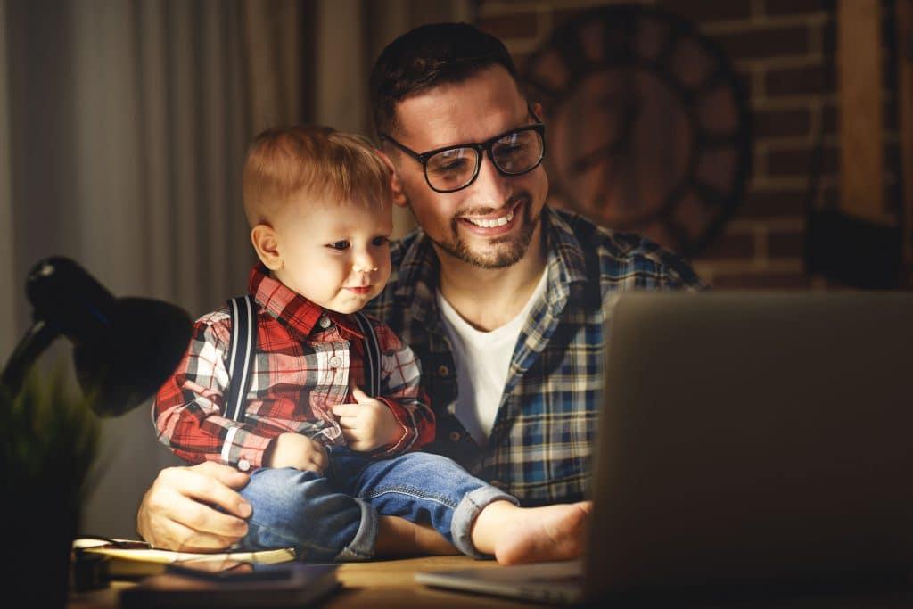Homem feliz, olhando para a tela de um computador aberto em cima de uma mesa, ao lado de uma criança pequena, que está sentada em cima da mesa.