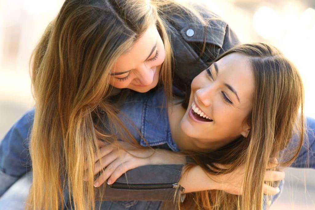 Duas mulheres, sorridentes, uma pulando nas costas da outra, brincando enquanto se cumprimentam.