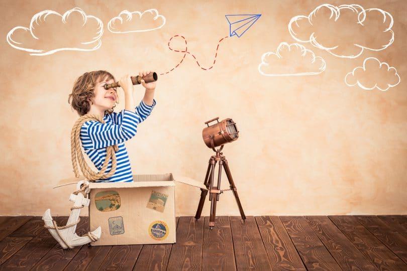 Criança dentro de uma caixa de papelão com binóculo na mão e corda em volta dos brações com desenhos de nuvens e aviãozinho de papel