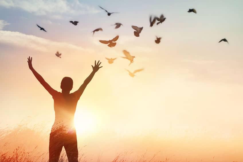Mulher com braços abertos e pássaros voando ao fundo