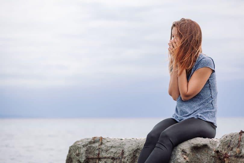 Mulher com mão no rosto e cabelo ao vento sentada em uma pedra com mar ao fundo