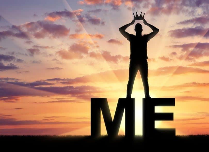 """Homem coroando a si mesmo em cima de duas letras formando a palavra """"ME"""", """"eu"""" em português."""