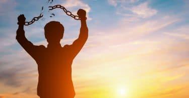 Silhueta de menino com correntes nos brações quebradas e céu azul e sol ao fundo