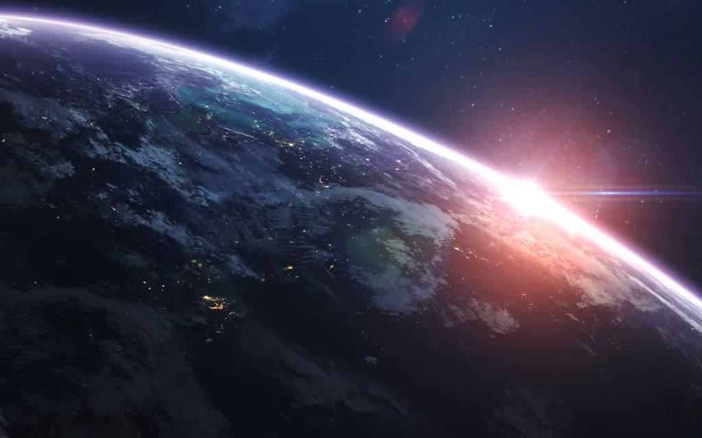 Imagem do planeta terra visto de fora com o sol nascendo atrás.