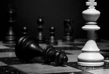 Peças de xadrez, uma rainha preta caída e um rei branca em pé