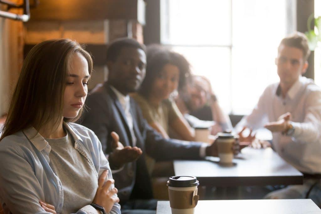 Menina branca sentada ao lado de seu grupo de amigos, formado de pessoas de diversas etnias, chateada.