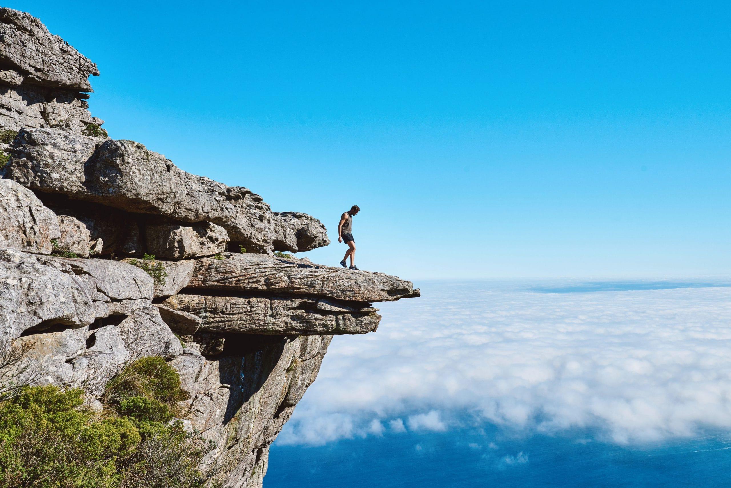 Homem caminha para a ponta de uma pedra, como se estivesse prestes a pular no abismo.