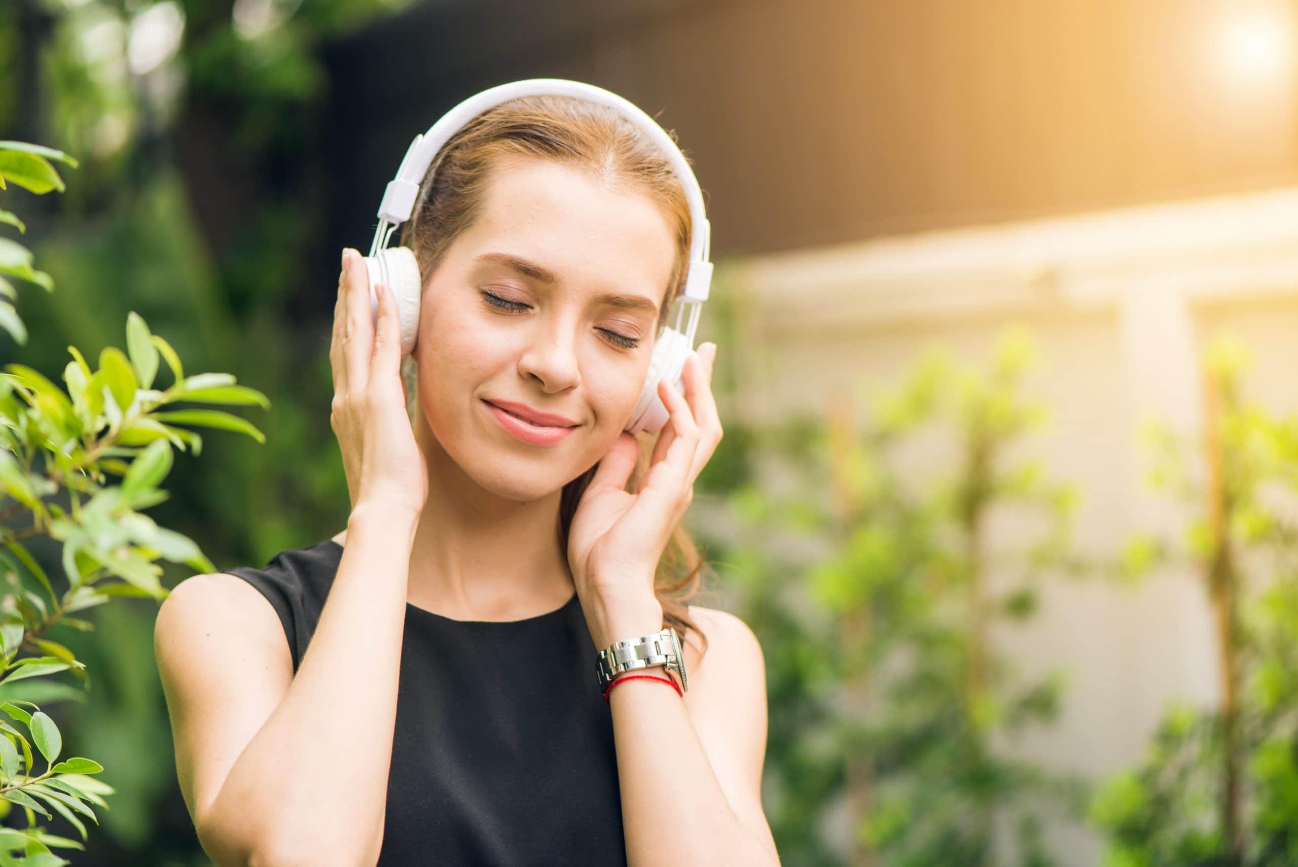 Mulher jovem ouvindo música no fone de ouvido em meio a um ambiente cheio de plantas.