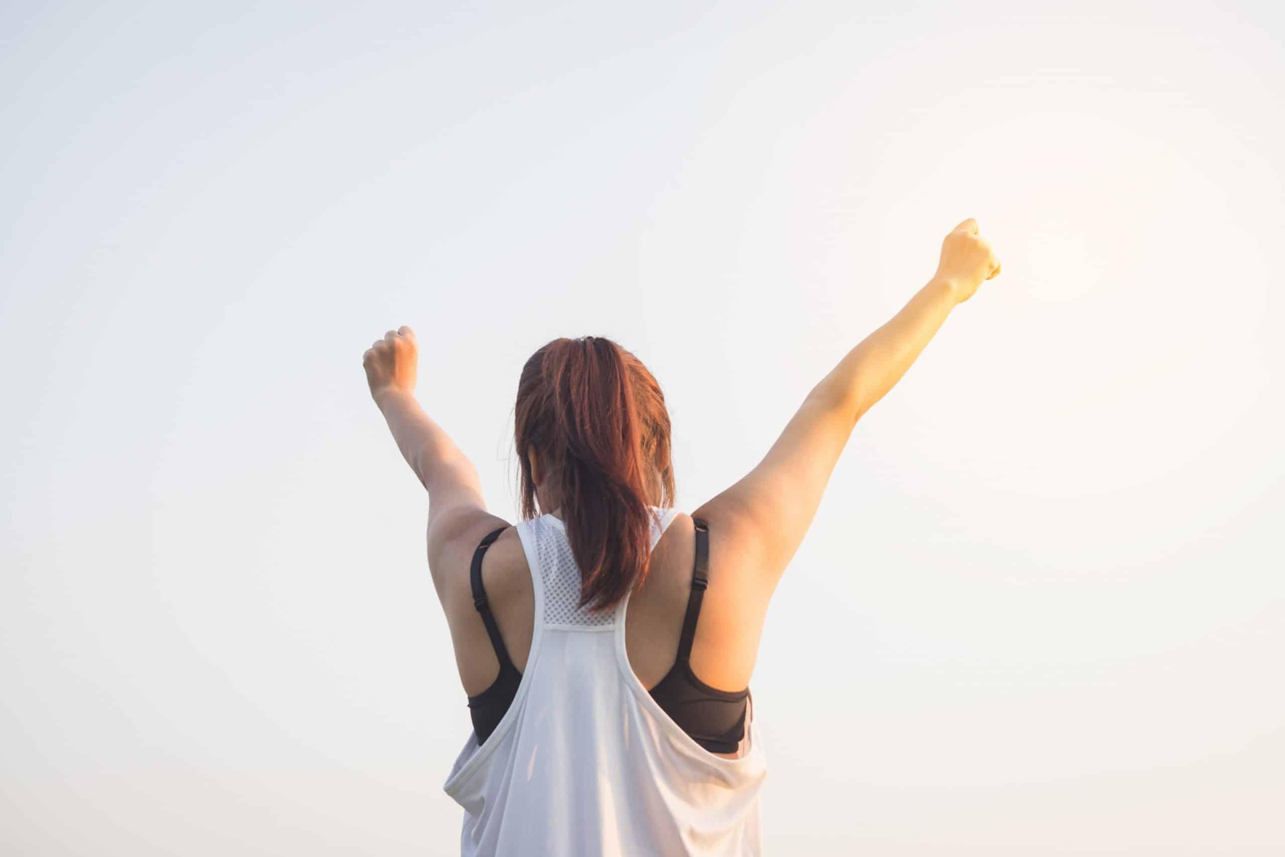 Mulher de costas levantando as mãos para o céu com os punhos fechados, em sinal de vitória.