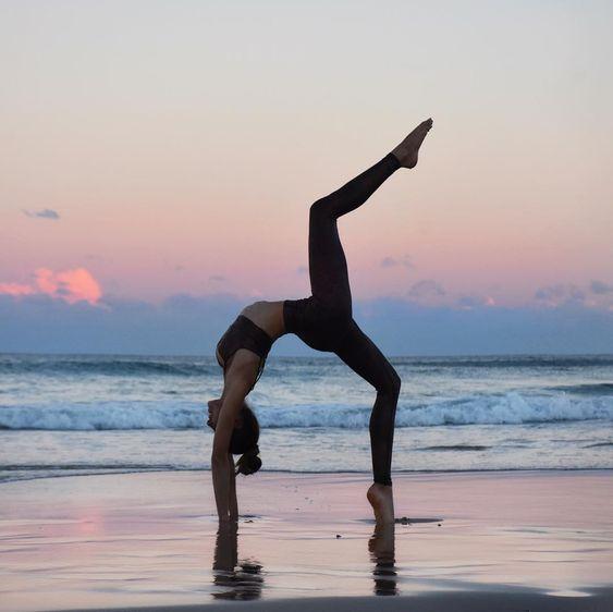 mulher fazendo ioga na praia