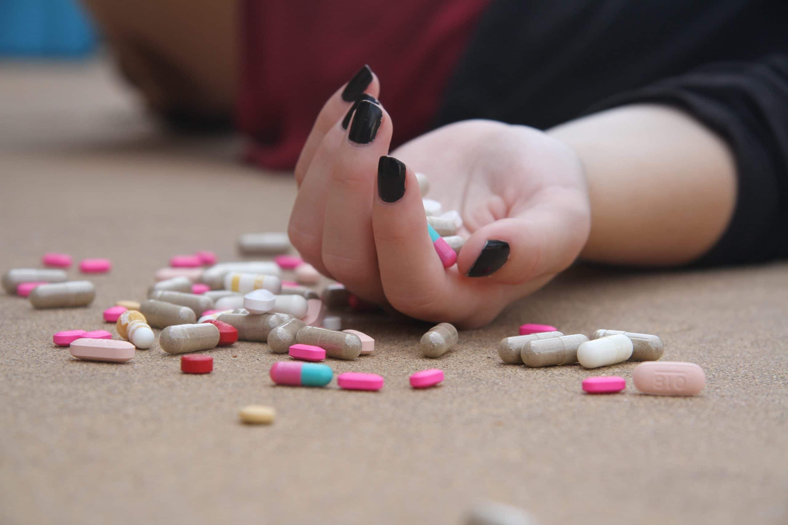 Mão de uma mulher caída no chão, segurando vários comprimidos que se espalham pela superfície., indicando uma tentativa de suicídio.