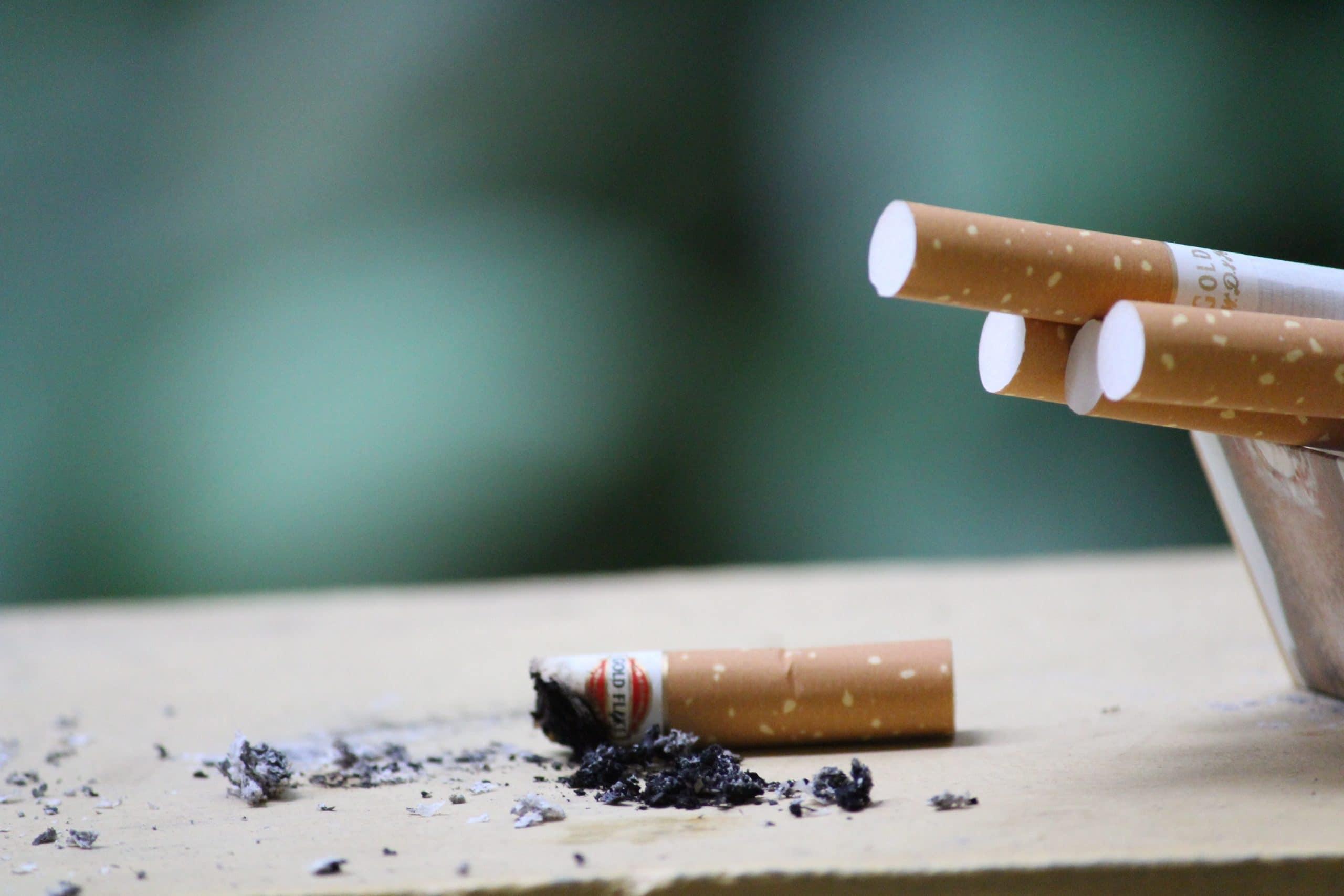Cigarro apagado sobre uma superfície bege, com as cinzas espalhadas. Ao lado direito, quatro cigarros inteiros sobrepostos uns aos outros estão dentro de um recipiente.