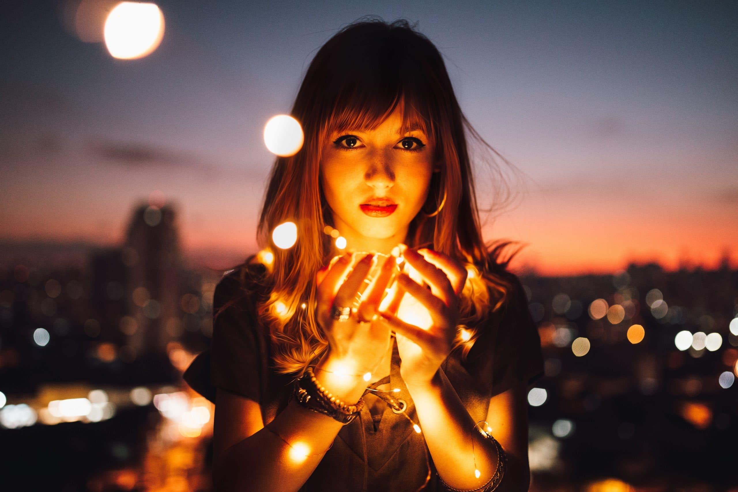 Mulher segurando luzes nas mãos em frente a uma cidade durante a noite.