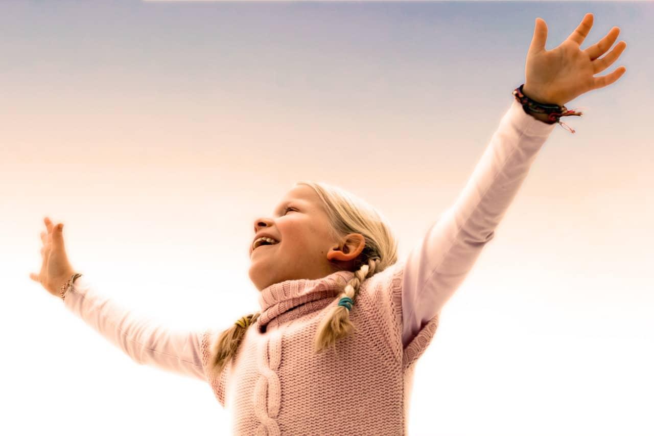 Menina vista de baixo com braços para cima sorrindo