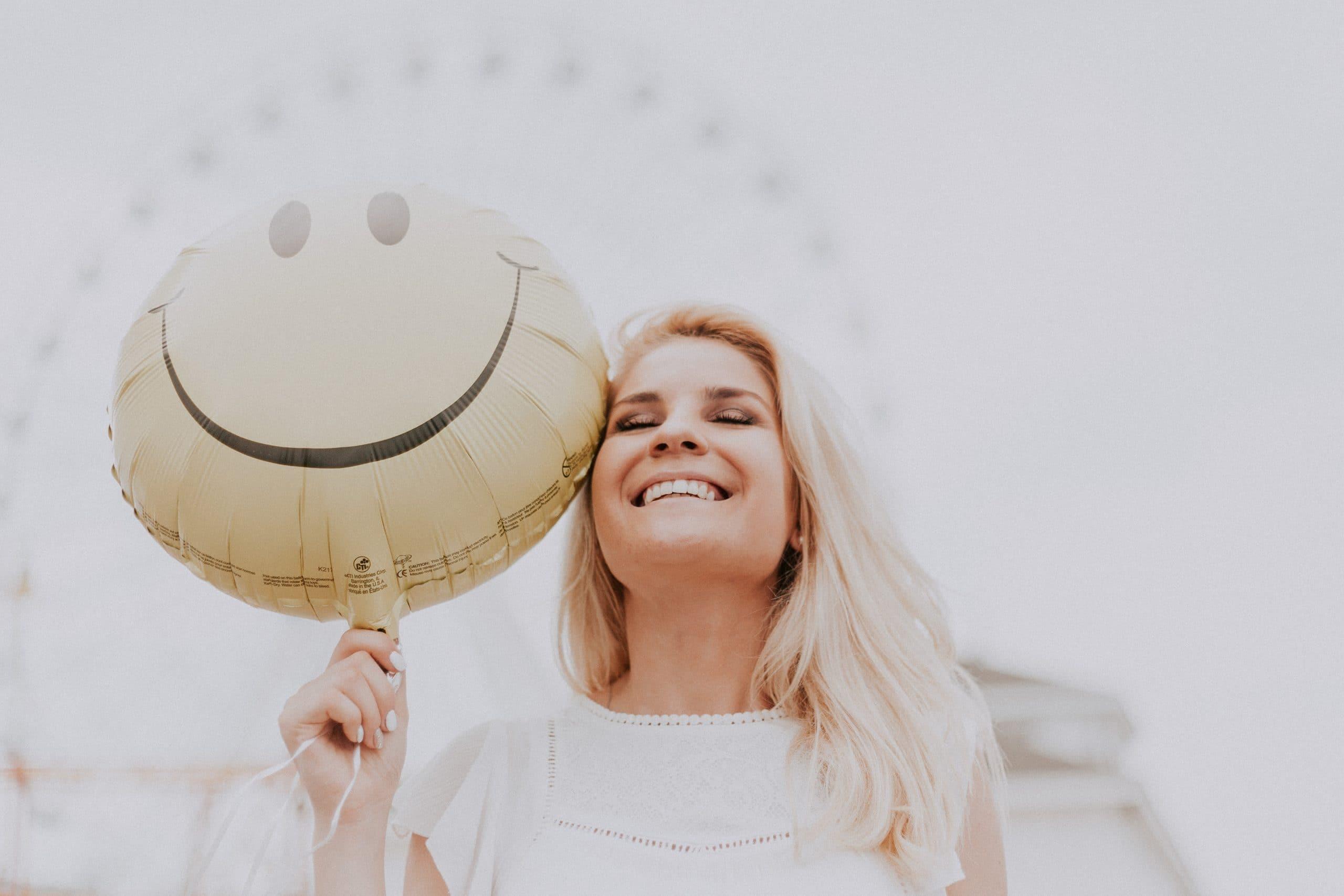 Mulher em um parque de diversões segurando um balão com o desenho de um rosto feliz.
