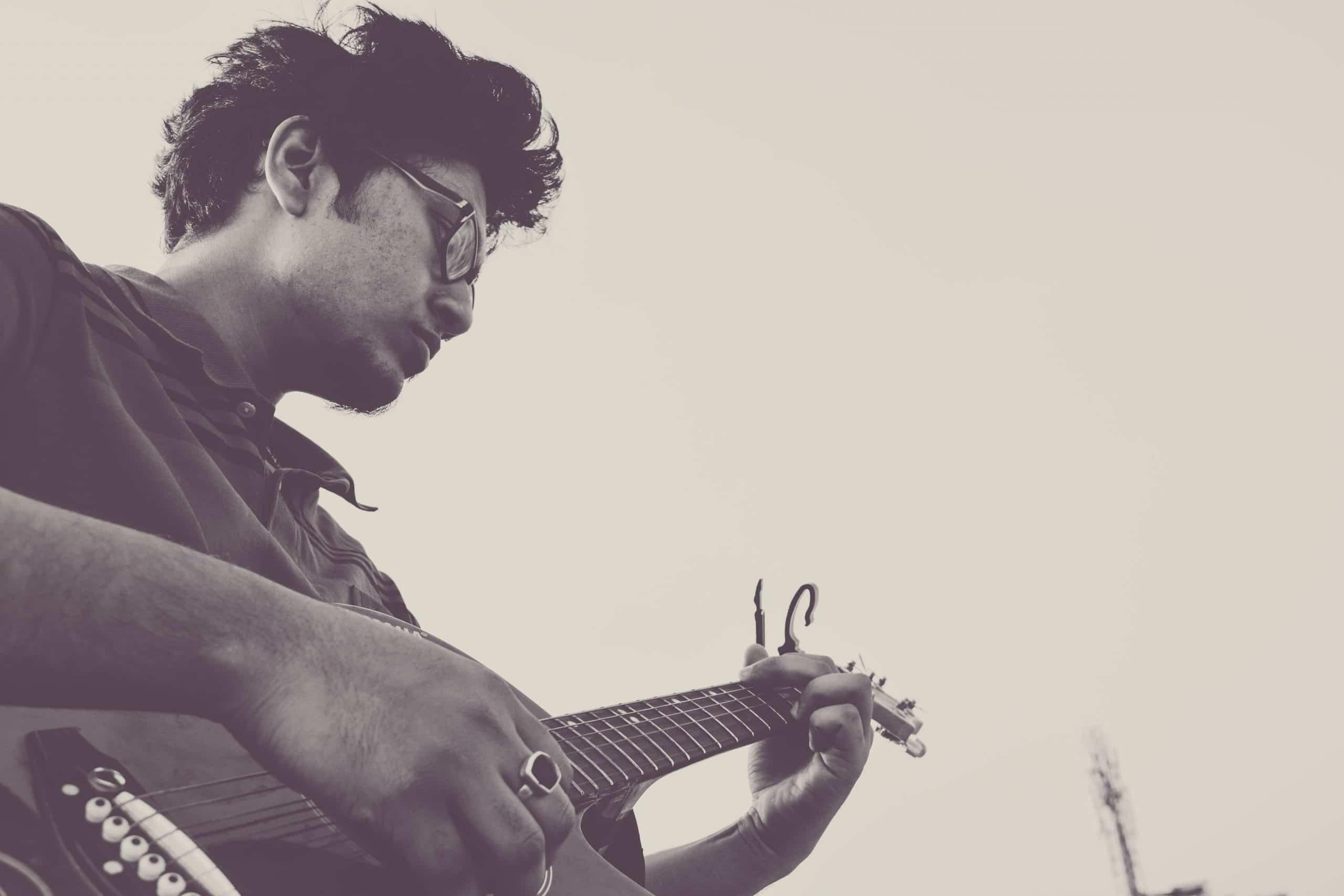 Homem jovem de óculos tocando música em uma guitarra.