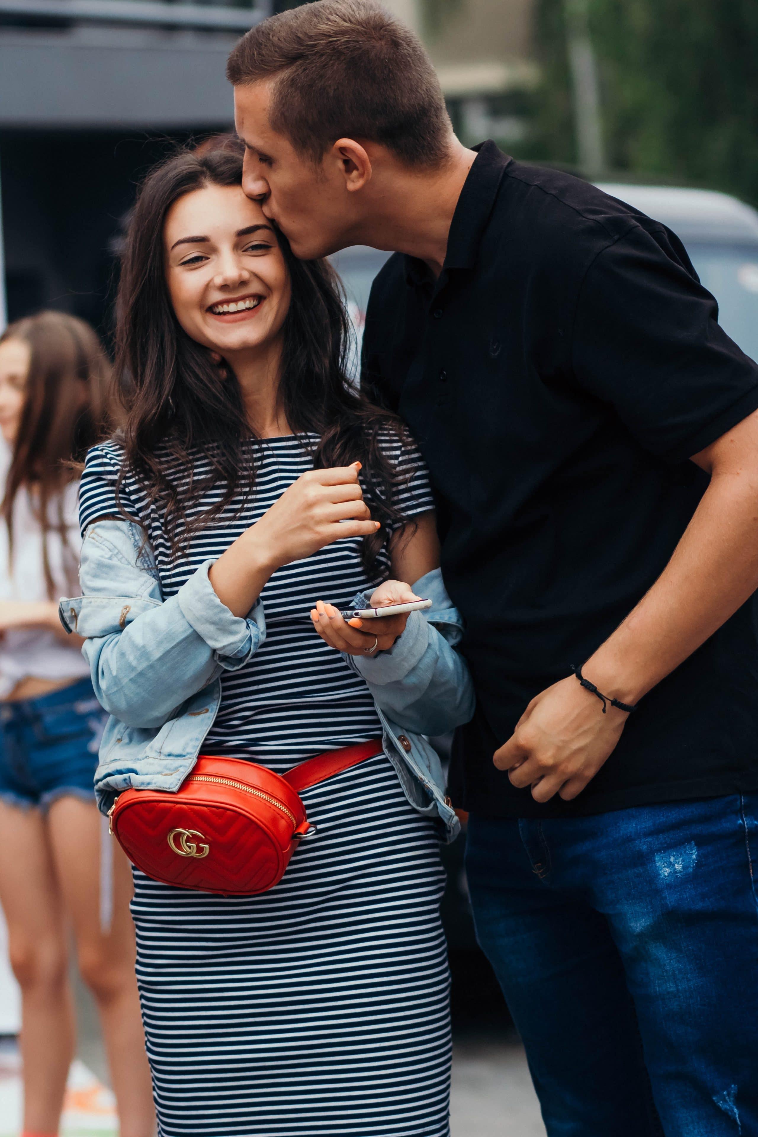 Homem de camisa preta dá um beijo carinhoso na testa de namorada com vestido listrado, jaqueta jeans e bolsa vermelha.
