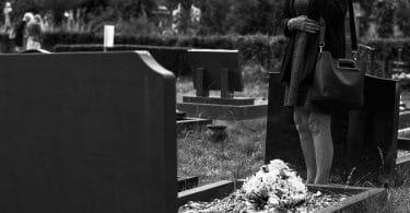 Mulher em pé em frente a um túmulo em um cemitério, demonstrando luto e tristeza.. Sua mão está cobrindo o rosto e há um buquê de flores sobre o túmulo.
