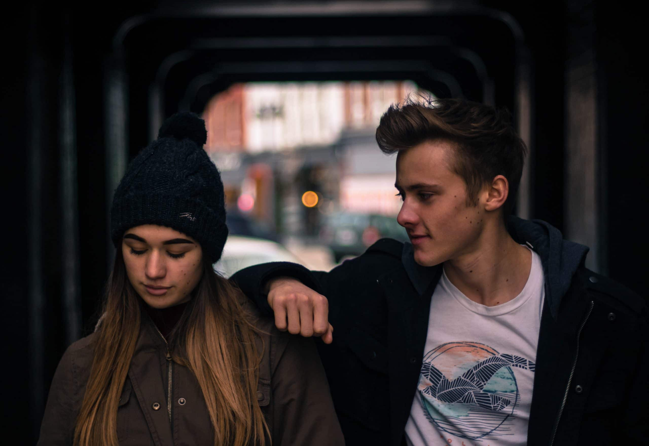 Casal em frente a uma janela. O garoto apoia seu braço no ombro da garota e a observa. A garota olha para baixo.
