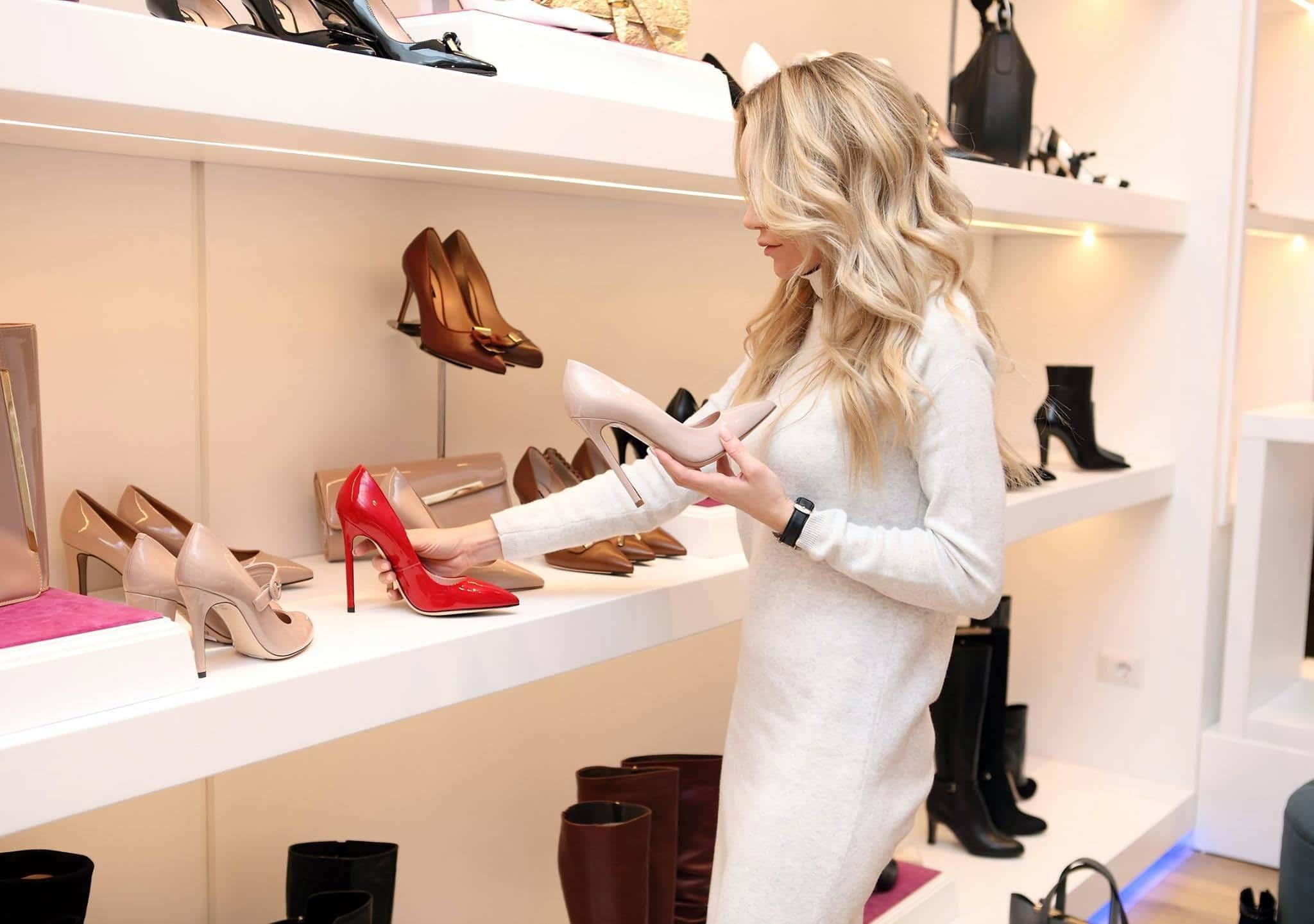 Mulher escolhe entre um salto rosa claro e um vermelho na prateleira de uma loja de sapatos.
