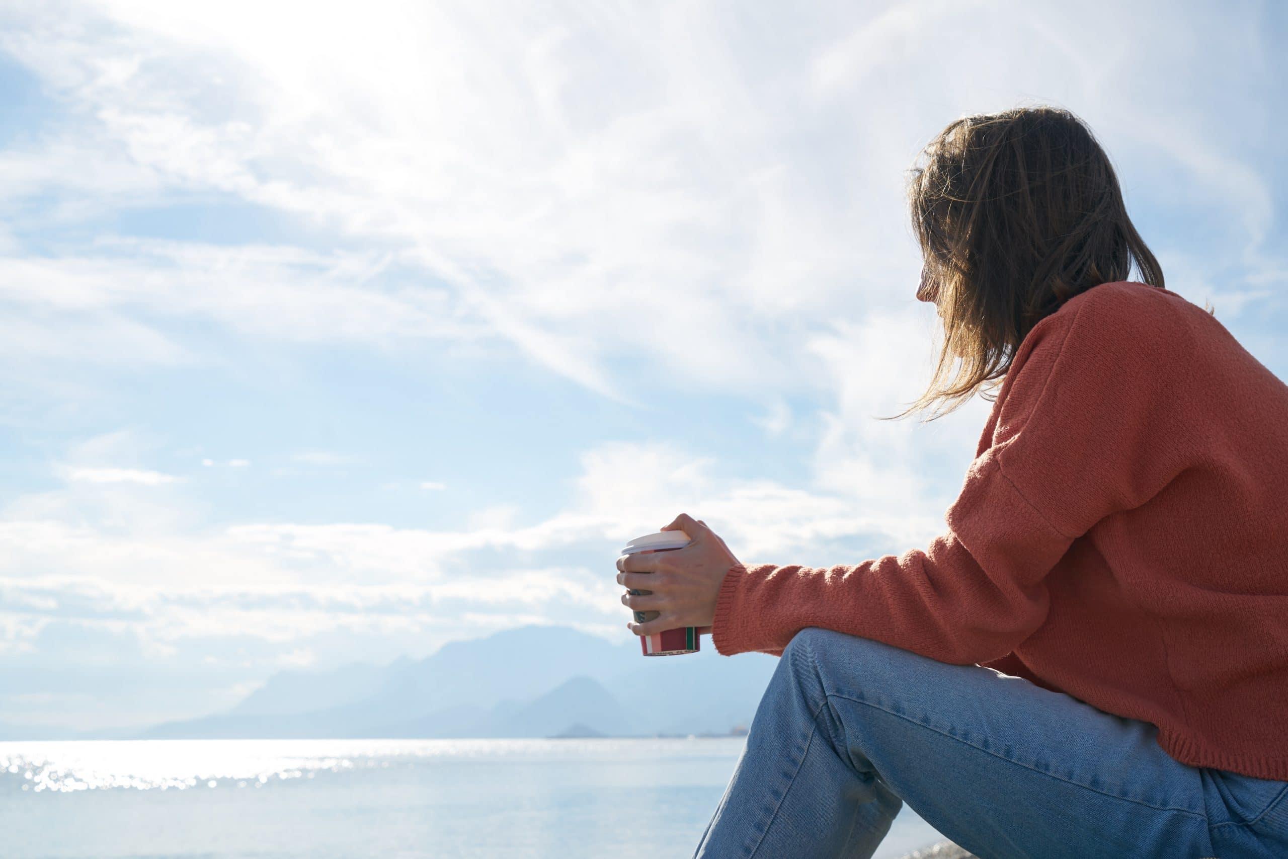 Mulher sentada na praia observando o horizonte, com um copo de café na mão.