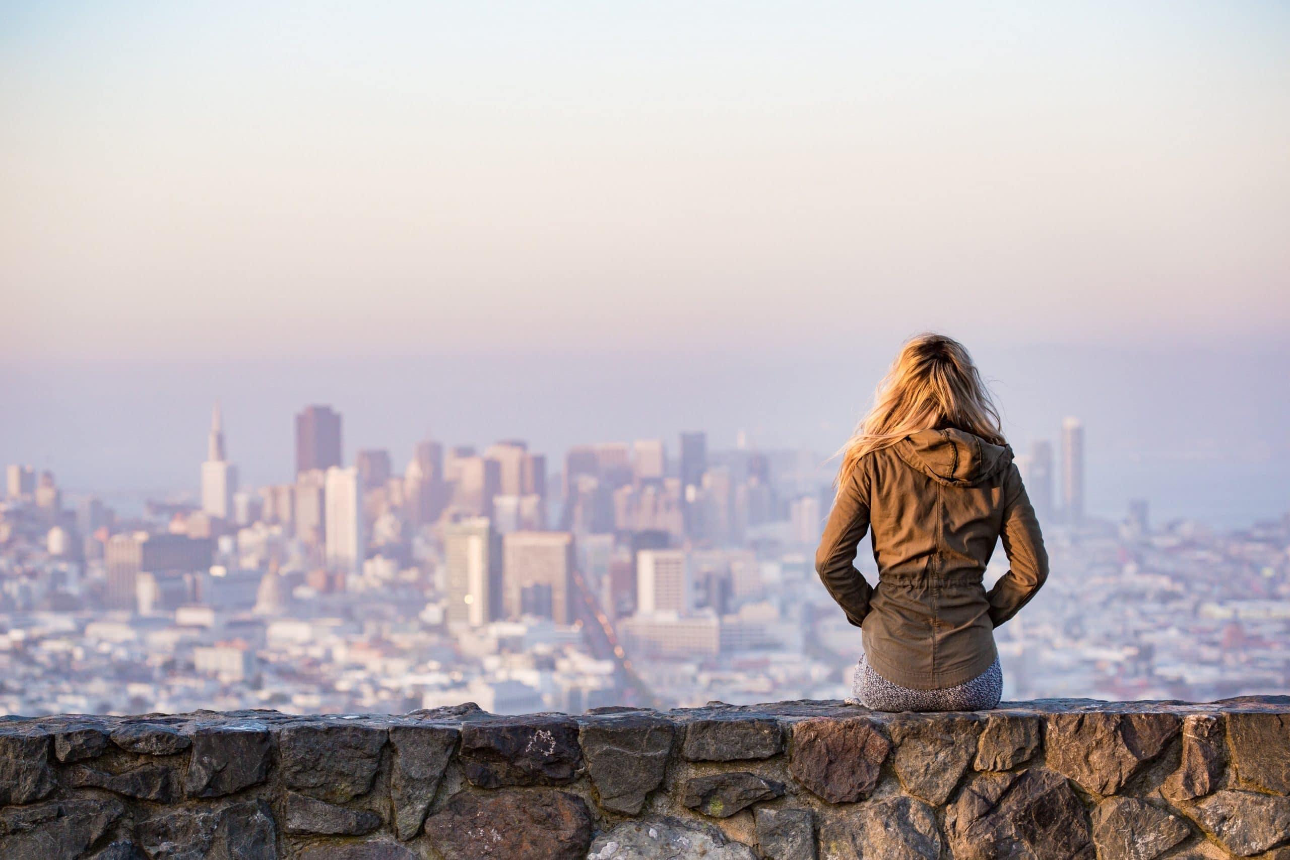 Mulher sentada sobre um muro, com roupas de frio, de costas, observando a cidade.