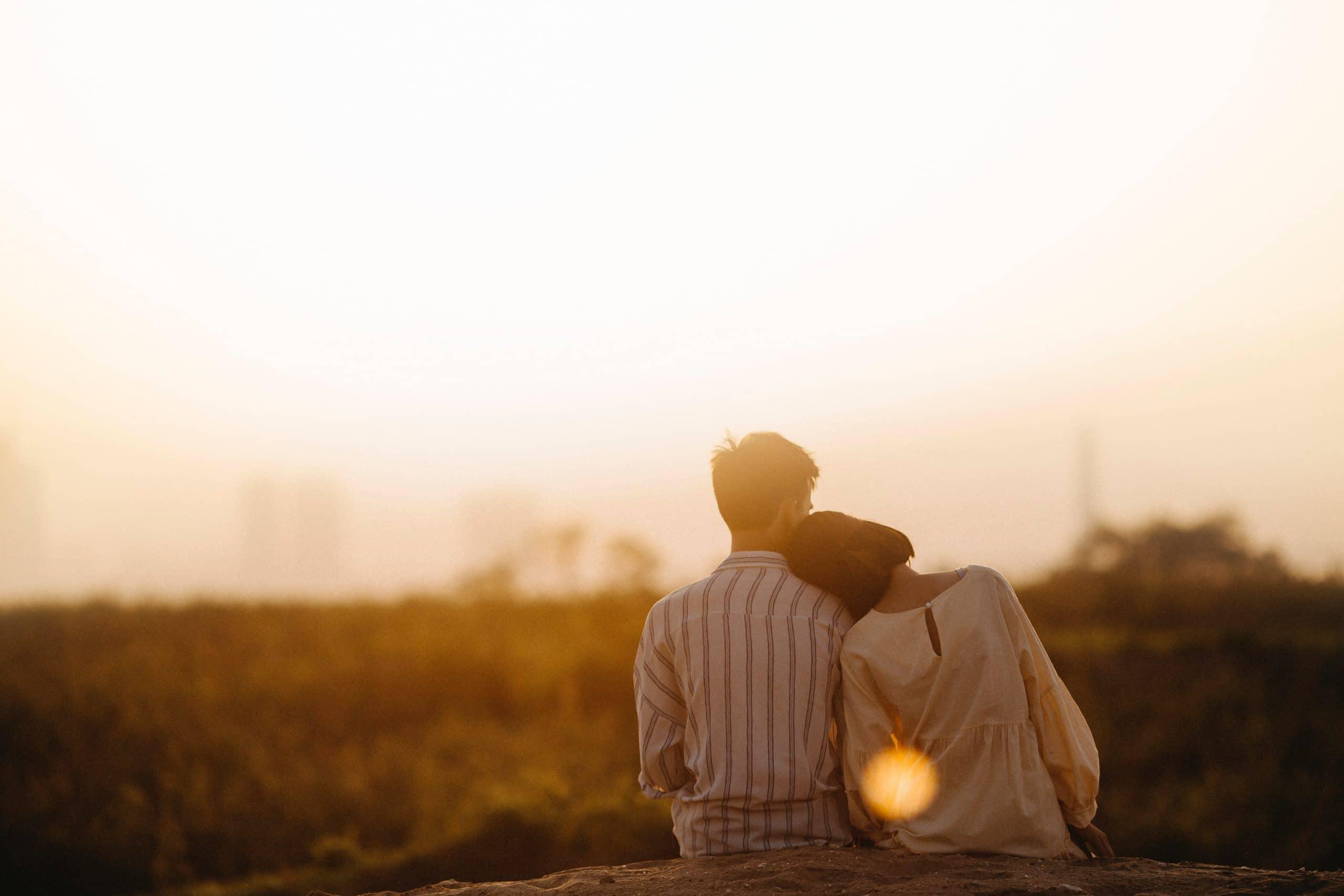 Casal sentado lado a lado observando o horizonte ensolarado. Garota encosta sua cabeça no ombo do garoto.