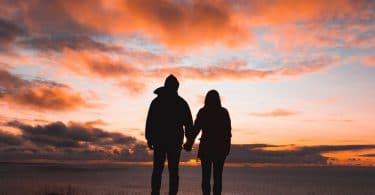 Casal de costas de mãos dadas com por-do-sol de fundo