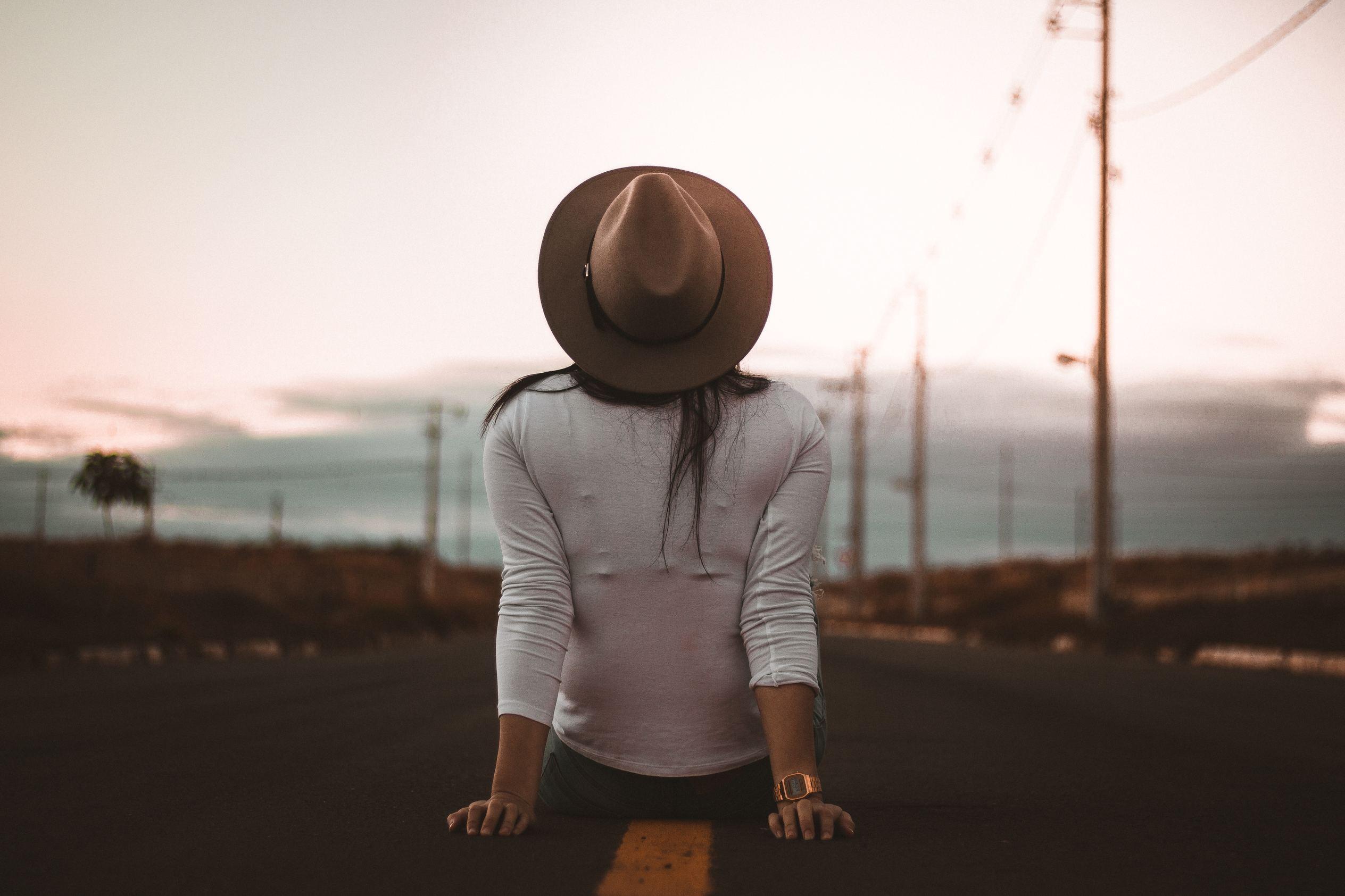 Mulher de costas sentada no meio de uma estrada com chapéu