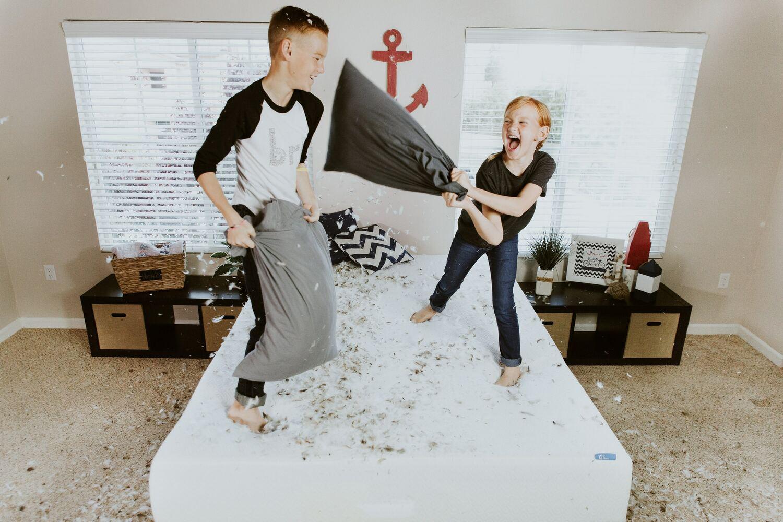 Menino e menina fazendo guerra de travesseiros em cima da cama
