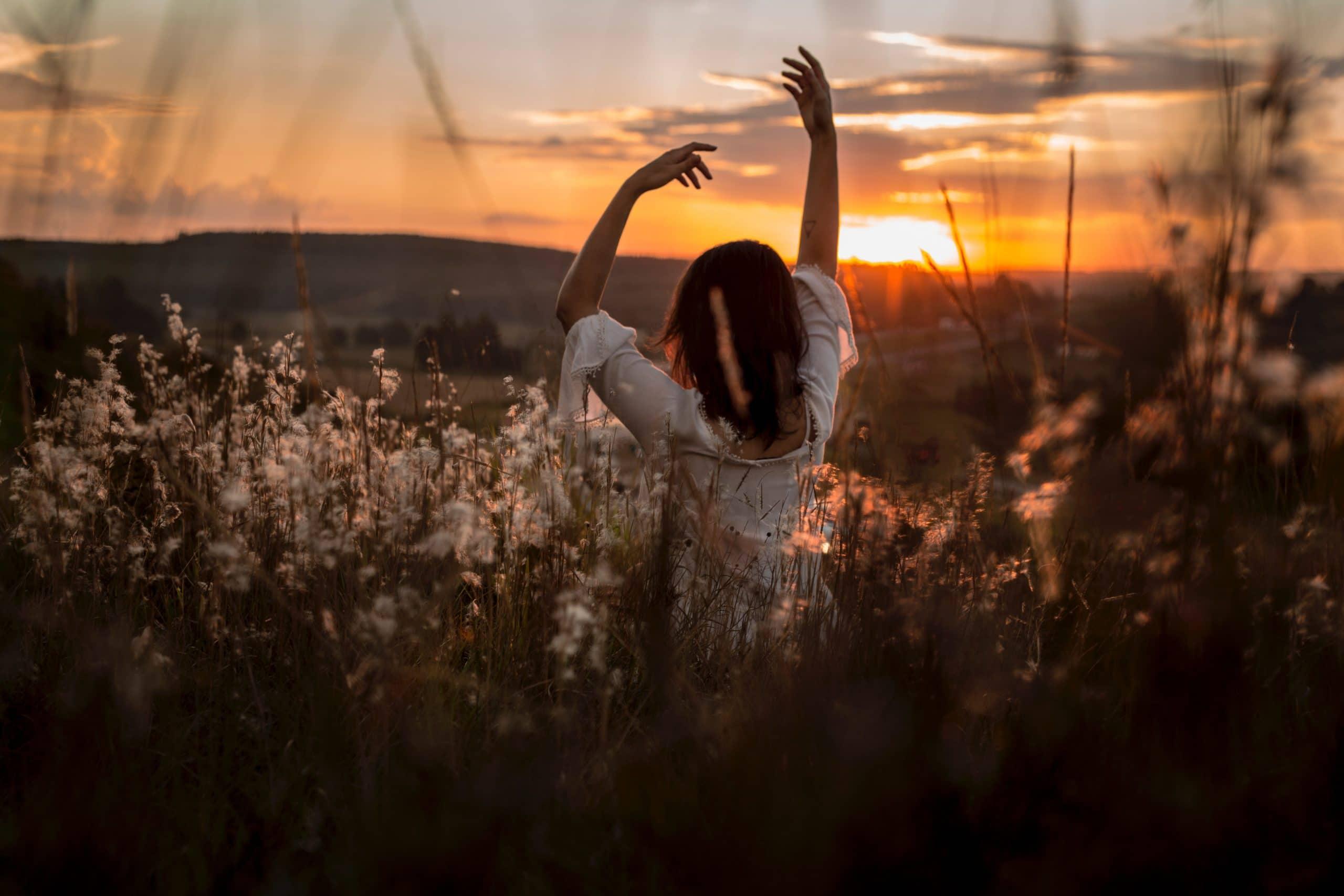 Mulher de costas com braços levantados no meio de plantação de algodão com pôr-do-sol de fundo