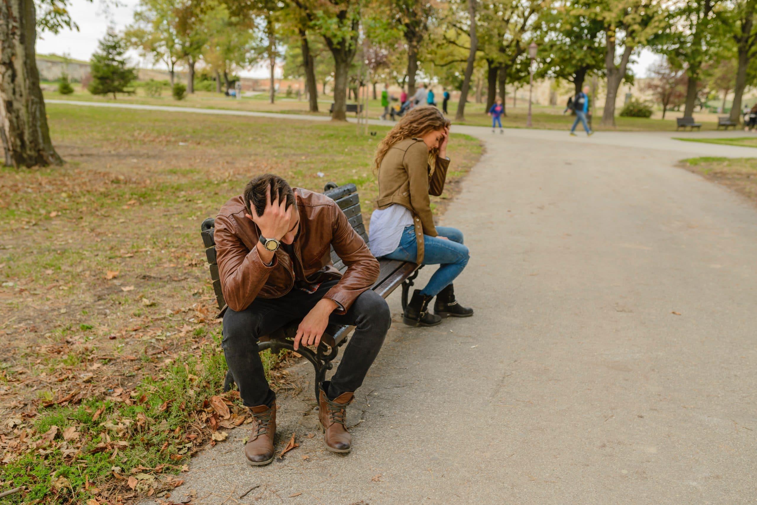 Casal distante um do outro, sentados no banco de um parque. Cada um está em uma ponta, com a cabeça sobre as mãos, em sinal de desentendimento.