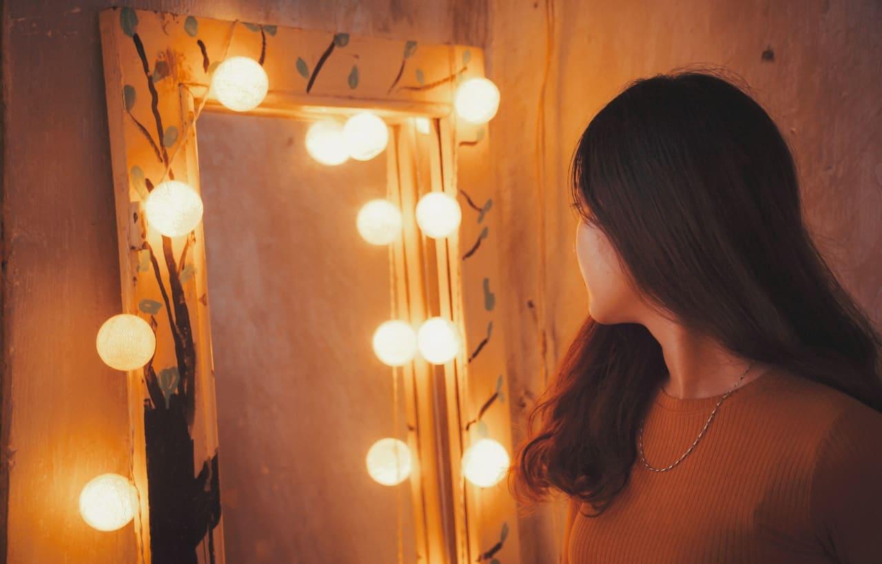 Menina de costas sem mostrar o rosto com espelho com luzes acesas em volta